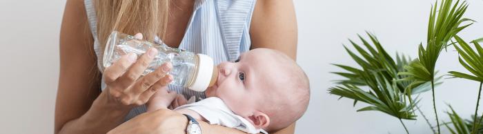 bébé boit biberon